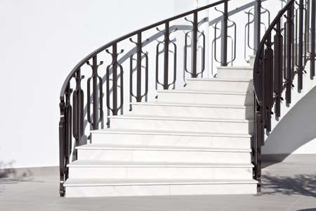 white stairways and black ornate fence