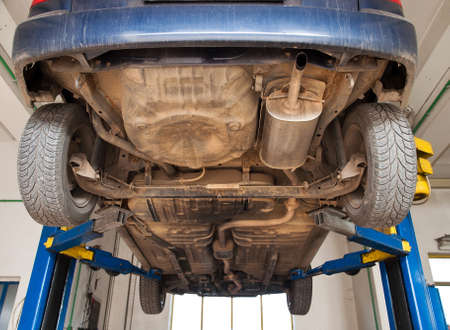 reparations: car lifted on repair stand in mechanic garage