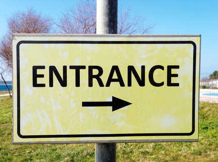 signage outdoor: entrance sign with black arrow