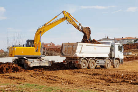 industrial excavator loading tipper truck on construction site