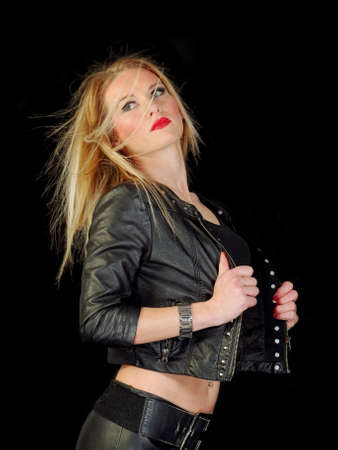 glamorous young woman in black leather jacket on black background, studio shot Stock Photo