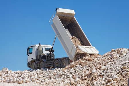 camion volteo: rocas volquete de descarga trituradas Foto de archivo