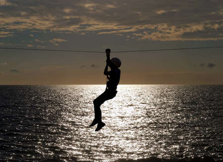 silhouette of young girl on zip line in summer sundown