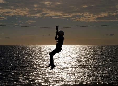 Silhouette der jungen Mädchen auf Seilrutsche im Sommer Sonnenuntergang Lizenzfreie Bilder