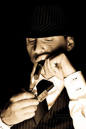 mystery man: young gangster with hat smoking cigar, studio shot