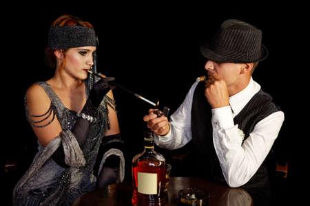 flapper: fumar chica de la aleta y gángster joven en el sombrero Foto de archivo
