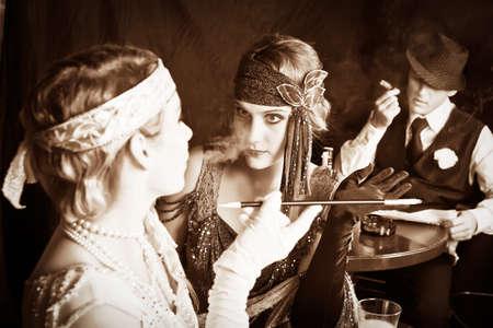 flapper: chicas flapper y joven gángster fumar en el bar