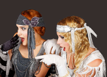 showgirl: two pretty flapper girls sitting and looking at someone