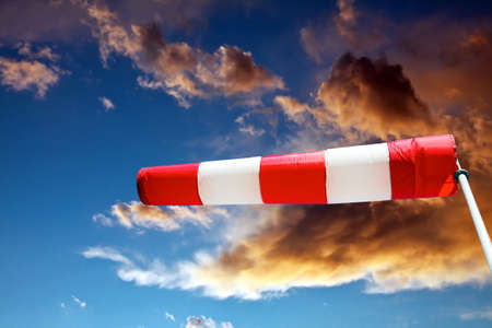 horizontally: horizontally flying windsock against stormy clouds Stock Photo