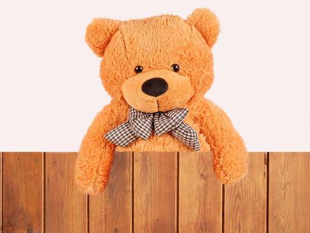 lazo regalo: esponjoso oso de peluche de felpa sobre la cerca de madera, tiro del estudio