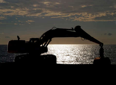 against the sun: Excavator standing against sun, silhouette image