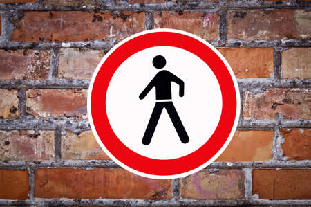 pedestrian sign: old red brick wall with no pedestrian sign