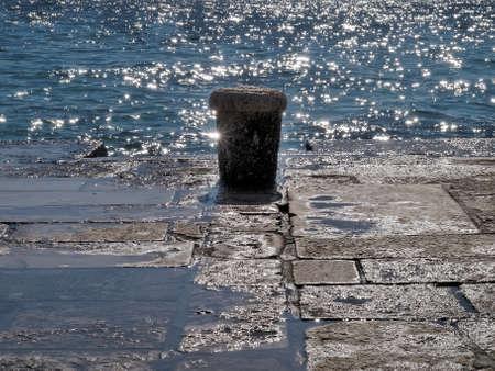 mooring bollard: old mooring bollard against sea