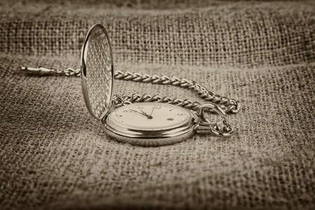 old golden pocket watch on burlap background, sepia tone
