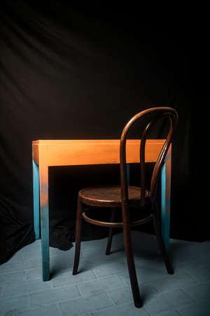 Vintage stoel en abstracte tafel tegen een donkere achtergrond