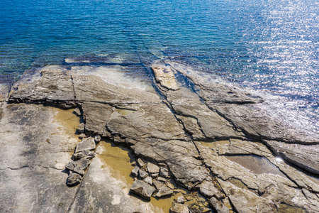 an aerial view of the beach with flat rocky cliffs immersed in the sea, Duga Uvala, Istria, Croatia