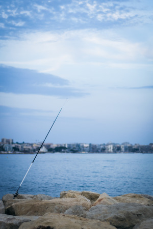 Fishing rod fixed on a stone coast in the front of a bay at Golfe Juan, Cote dAzur Imagens
