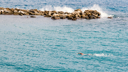 Man swimming in the sea in front of stone cliffs at Côte dAzur