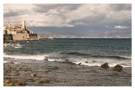 Vintage Style with waves at stone coast with mediterranean village in background Stock Photo