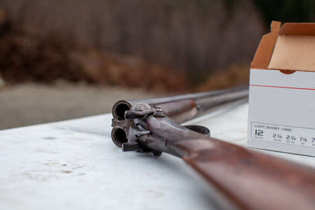 An old, vintage, break-action double-barrel shotgun featuring two triggers and two hammers. Placed on a table at an outdoor range with a box of ammunition (shot gun shells).