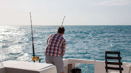 A man checks his fishing rods on a charter boat in Varadero, Cuba on a day excursion deep sea fishing in the Caribbean Ocean