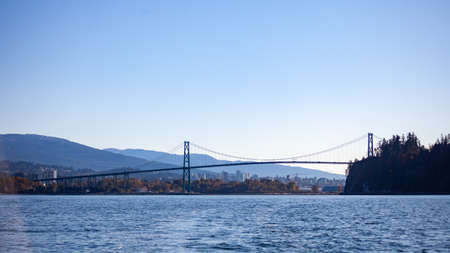 A view of North Vancouver, Stanley Park, and the Lion's Gate Bridge in British-Columbia, Canada. View taken from a sailboat leaving the harbor.