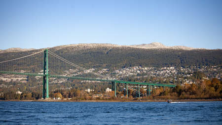 A view of the Lion's Gate Bridge and the North Shore mountains in the background taken from a boat on the water. Looking at North and West Vancouver, British-Columbia