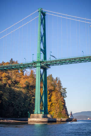 A close up view of the Lion's Gate Bridge and the Stanley Park in the background taken from a boat on the water. 스톡 콘텐츠