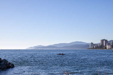 Two people enjoy a sunny day canoe ride out of Ambleside Beach, West Vancouver, British-Columbia with a view of English Bay, mountains and the city 스톡 콘텐츠