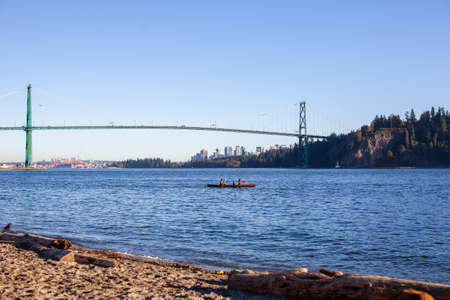 Two people enjoy a sunny day canoe ride out of Ambleside Beach, West Vancouver, British-Columbia with a view of English Bay, Lionsgate Bridge and downtown Vancouver 스톡 콘텐츠