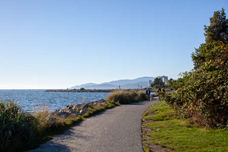 People enjoying the walking trails at Ambleside Beach in West Vancouver, British-Columbia, with views of West Vancouver and English Bay