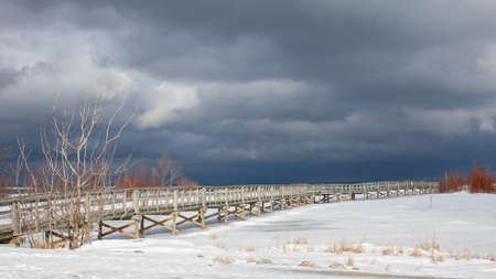 An old, wooden bridge crosses a section of frozen Georgian Bay waterfront in Collingwood, Ontario. The sky above is menacing and gloomy, with a winter storm approaching. Empty walking trail.