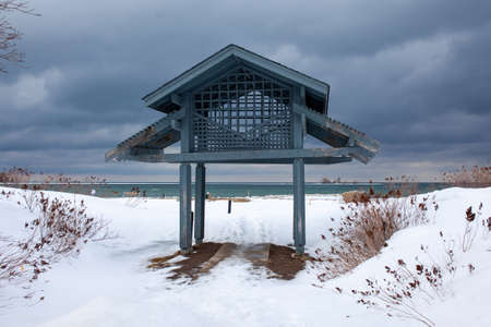 A garden pavilion (gazebo) overlooks southern Georgian Bay on a gloomy, stormy winter day in Lighthouse Point, Collingwood.