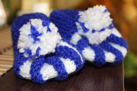 bootees: Knitted handmade baby s bootees on wood table
