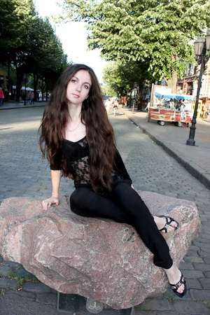 A girl with long hair sitting on a rock in the city photo