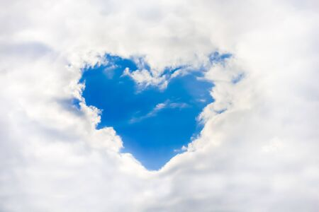 clouds making: Clouds making a heart shape againt blue sky. Love sign. Stock Photo
