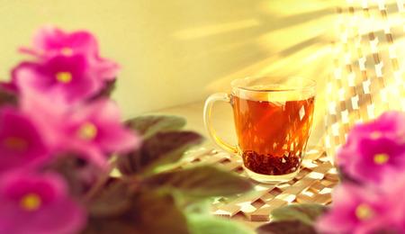 木製の背景に黒茶のガラスのコップ。朝。太陽の光は部屋に木製の格子を輝きます。前景にスミレのピンクの花がぼやけていると焦点が合っていま 写真素材
