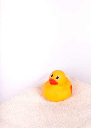 squeak: Rubber duck on white towel isolated on white Stock Photo