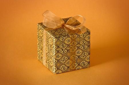 Little gold gift isolated on orange background Stock Photo