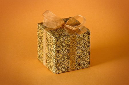 Little gold gift isolated on orange background Stock Photo