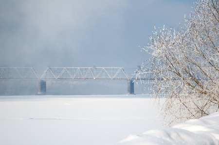 winter view on the riverside with railway bridge