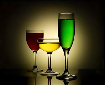 Different wine glasses with yellow, red and green beverages