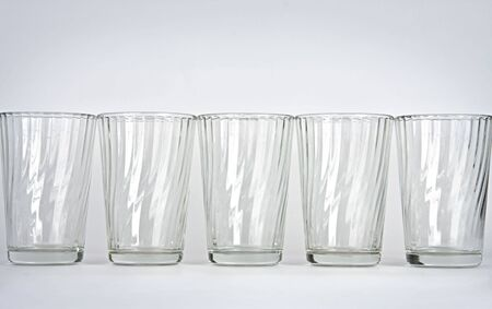 Five empty glasses on a white background