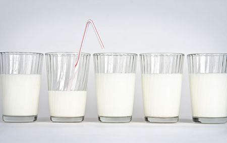 Vijf glazen op een witte achtergrond met melk
