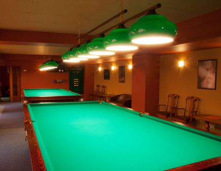 Interior of a club having billiard tables illuminated with lights photo