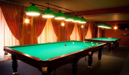 Interieur van een club met biljarten verlicht met lampen