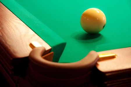 A white ball near the pocket of a billiard table Stock Photo