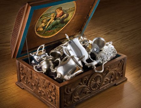 Carved chest with silver tableware Stock Photo