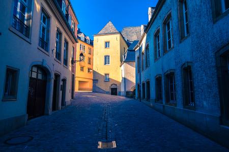 Straat in Luxemburg. Zonsondergang stralen op een oud gebouw. Stockfoto