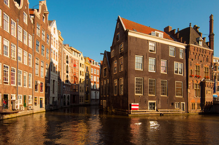 Traditional Dutch buildings reflecting on canal water at sunset Stock Photo